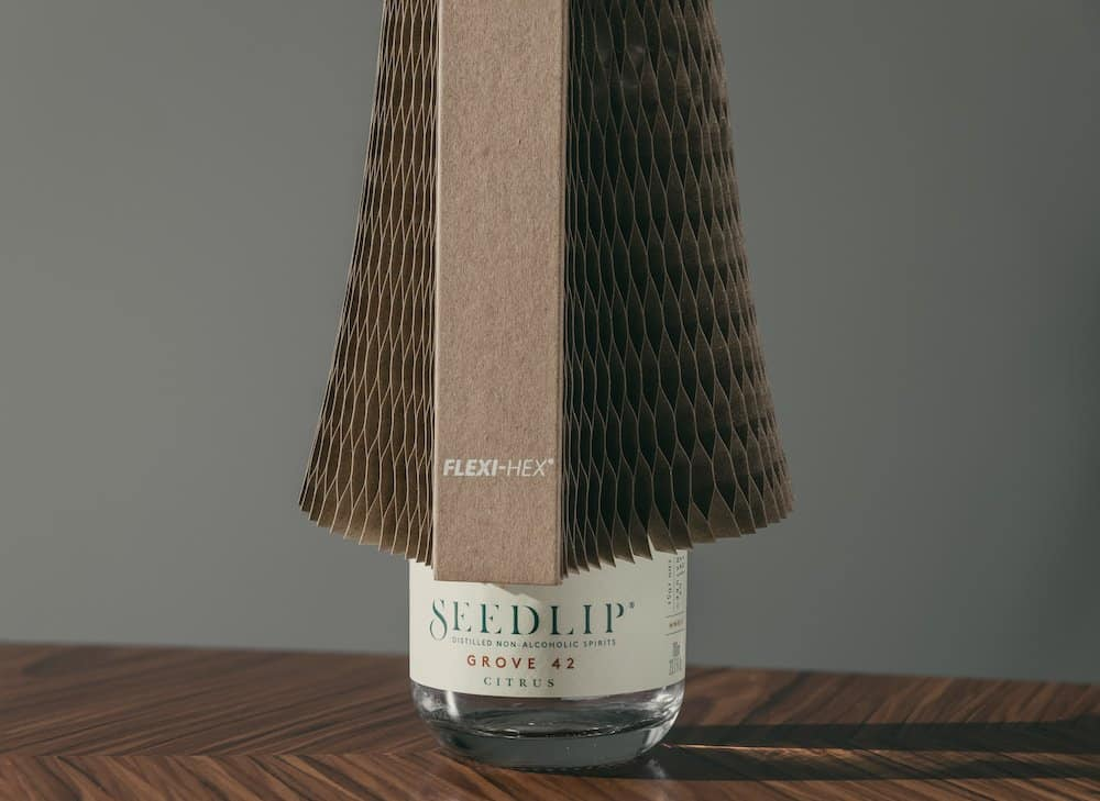 Flexi-Hex packaging being lowered onto a Seedlip bottle