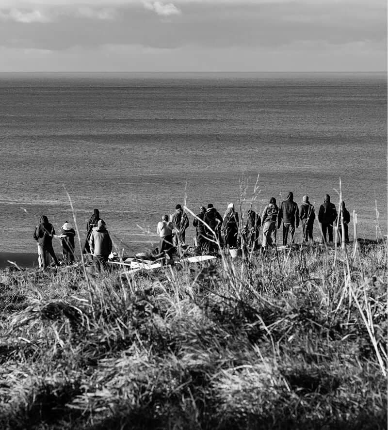 A crowd of people standing on a cliff watching surfing